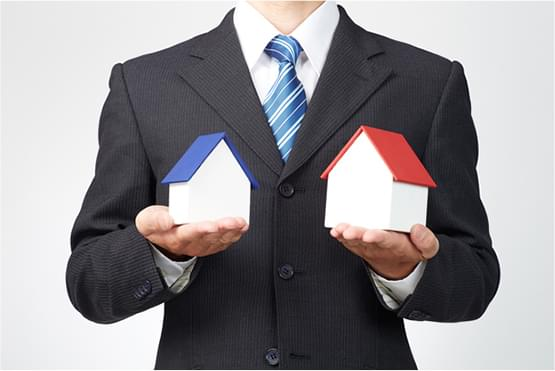 スーツの男性が両手の手のひらに家の模型を載せている写真