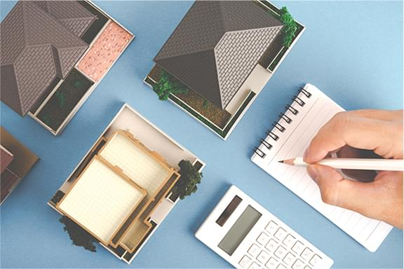 複数の住宅の模型とメモをとる手、電卓を俯瞰した写真