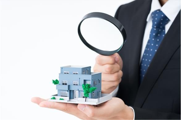 スーツを着た男性が掌の上にある家の模型を虫眼鏡で見ている写真