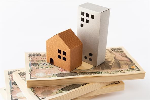 札束の上に置かれた家の模型の写真